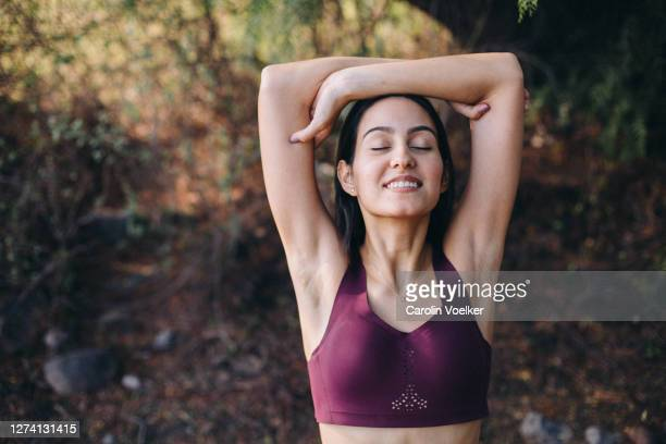 young latina woman stretching in nature after a workout with her arms raised - arms raised stock pictures, royalty-free photos & images