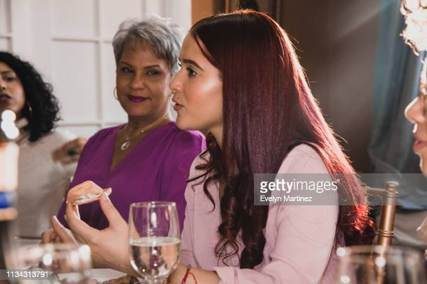 young latina woman talking at dinner party holding an appetizer in her hand. young woman in the frame has long red hair. woman next to her is smiling wearing a purple top. two other women in the periphery of dinner table. - evelyn martinez stock pictures, royalty-free photos & images