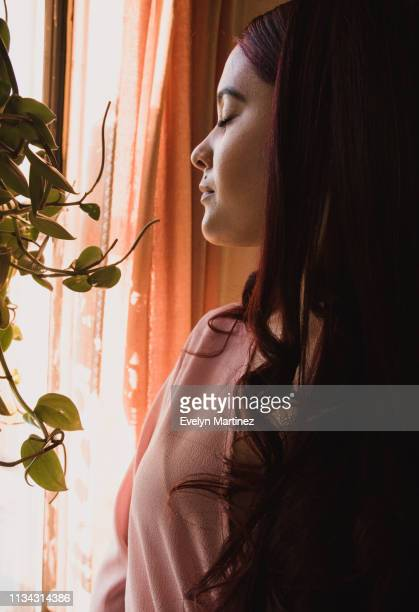 young latina woman with eyes closed standing in front of window. house plant and curtain in the frame. - evelyn martinez stock pictures, royalty-free photos & images