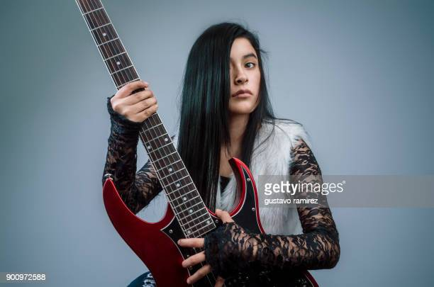 young latina woman with red guitar