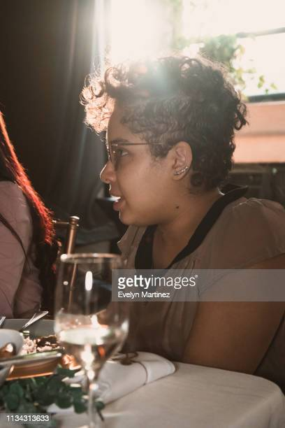 young latina woman with short dark blonde hair talking at the dinner table. sun beam from window. glass, napkin, plate and flatware in the frame. - evelyn martinez stock pictures, royalty-free photos & images