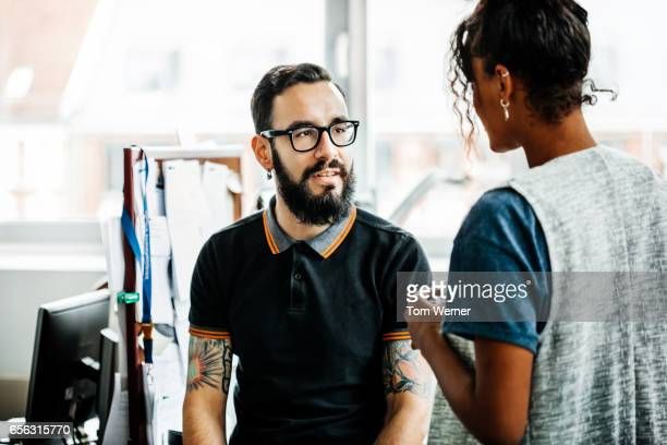 Young lating businessman in casual wear talking with colleague in an office
