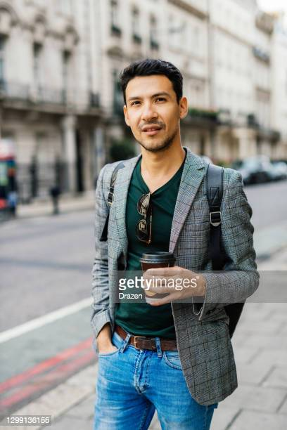 young latino man in london, crossing the busy street while multi tasking - one mid adult man only stock pictures, royalty-free photos & images