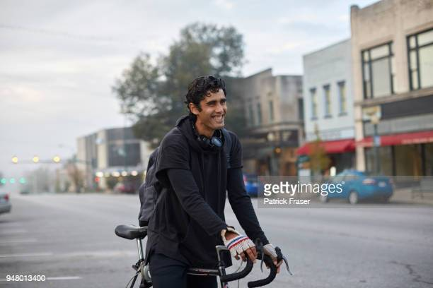 Young Latino man stands smiling with bike in small town square