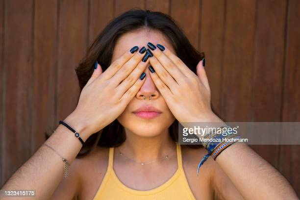 young latino woman covering her eyes, see no evil, brown wooden background - color blindness - fotografias e filmes do acervo