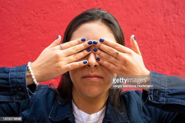 young latino woman covering her eyes. see no evil, red background - color blindness - fotografias e filmes do acervo