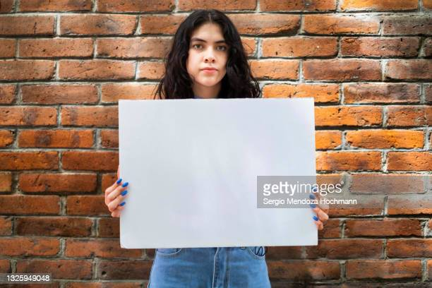 young latino woman holding a blank sign - brick wall background - person holding blank sign stock pictures, royalty-free photos & images