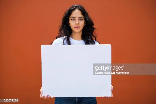young latino woman holding a blank sign - person holding blank sign stock pictures, royalty-free photos & images