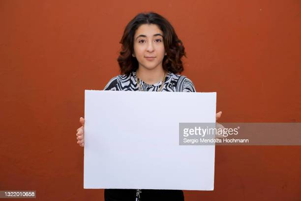 young latino woman holding a blank sign, red background - person holding blank sign stock pictures, royalty-free photos & images