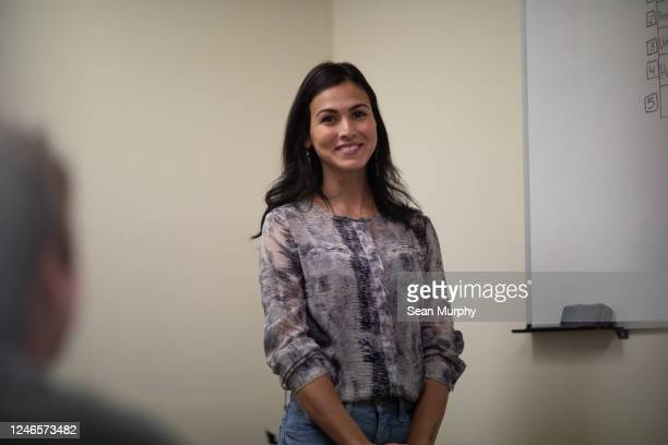 Young latino woman smiling at camera during business meeting.