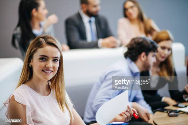 Young latinx businesswoman with her coworkers in the background