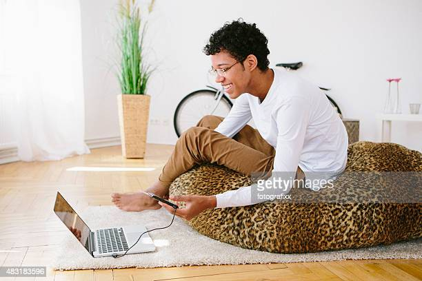 young laughing african man looks in his laptop, card reader