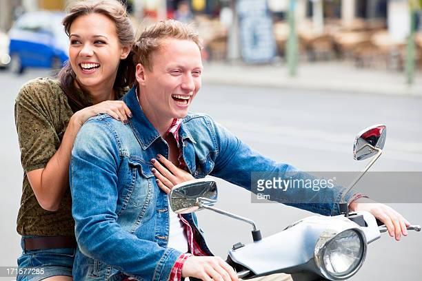 Junge Spaß paar Reiten Roller Throug die Stadt