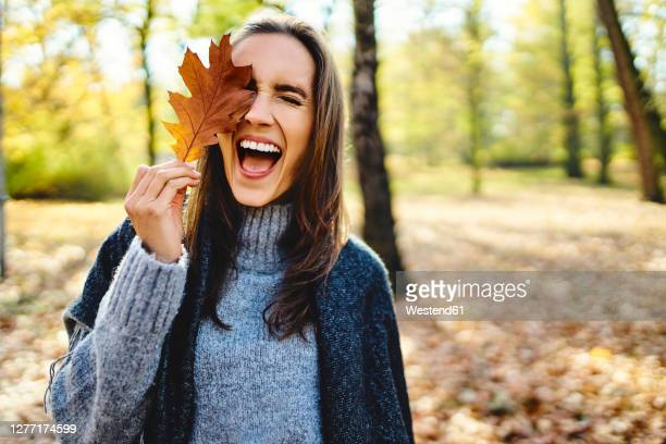 young laughing woman holding autumn leave on her eye - herfst stockfoto's en -beelden