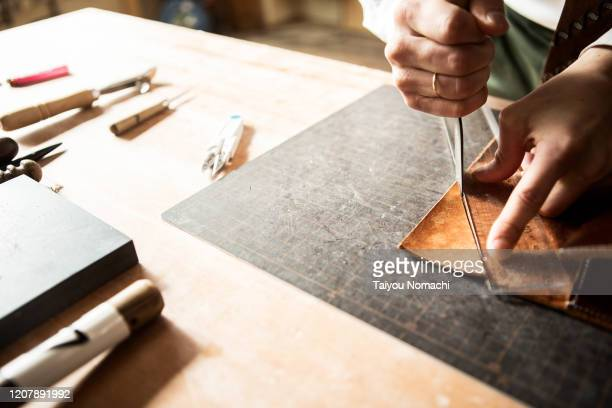 young leather craftsman making a bag - craftsperson stock pictures, royalty-free photos & images