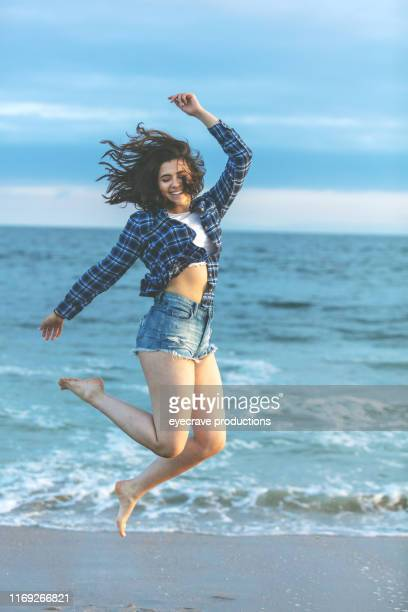 young Lebanese woman enjoying Seal Beach in California jumping in ocean waves and water