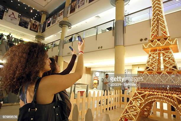 Young Lebanese women take pictures with their mobile phones of a matchstick model of the tallest Eiffel Tower constructed by wheelchairbound Lebanese...