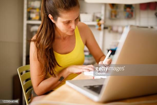 joven zurda mujer escribiendo durante una clase en línea - cola de caballo cabello recogido fotografías e imágenes de stock