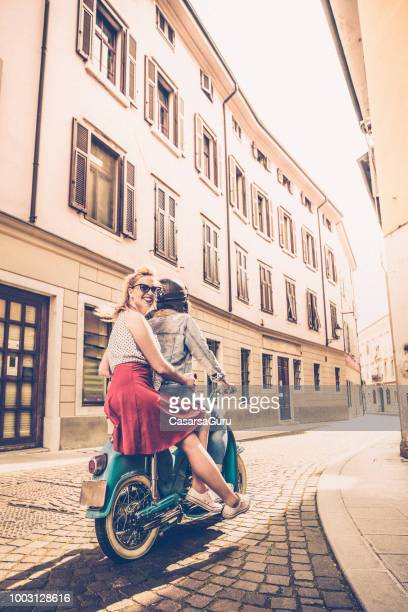 young lesbian couple driving old-fashioned motor scooter on italian city streets - vintage lesbian photos stock pictures, royalty-free photos & images