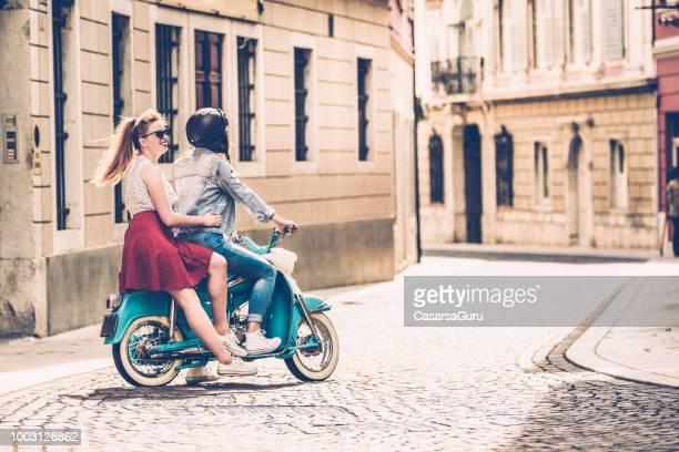 jeune couple de lesbiennes vieux moteur scooter de conduite sur les rues de la ville italienne - mobylette photos et images de collection