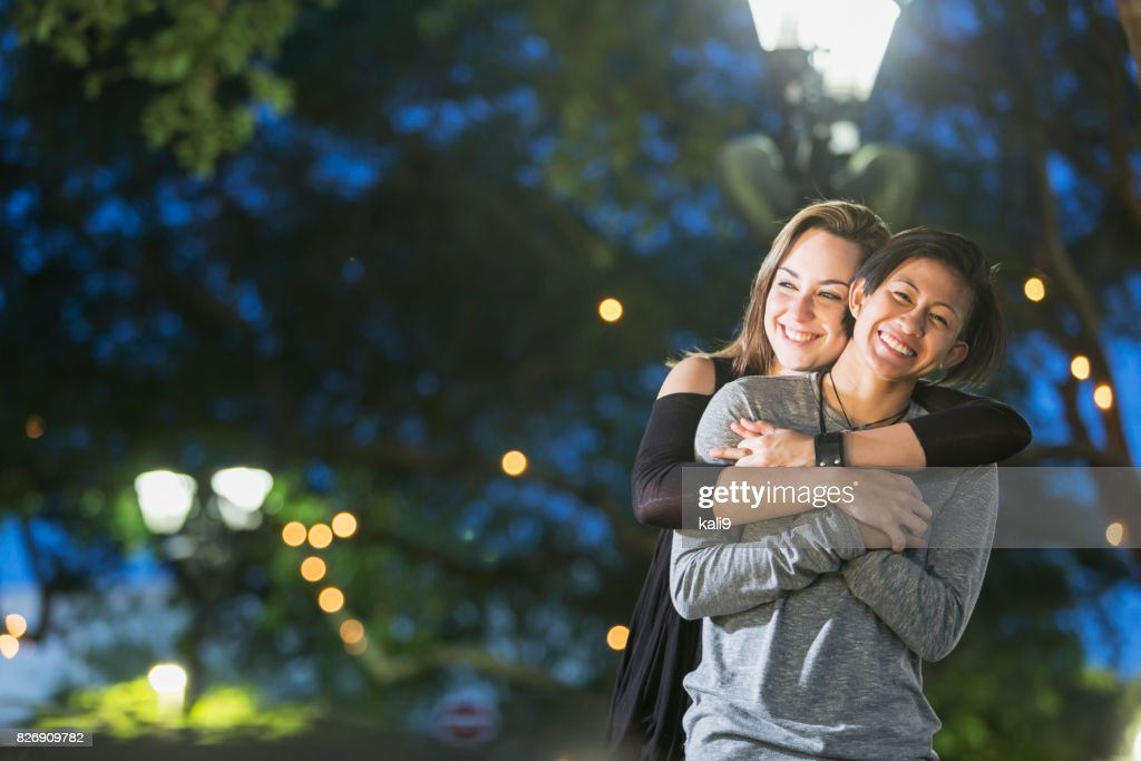 Young lesbian couple, outdoors at night : Stock Photo