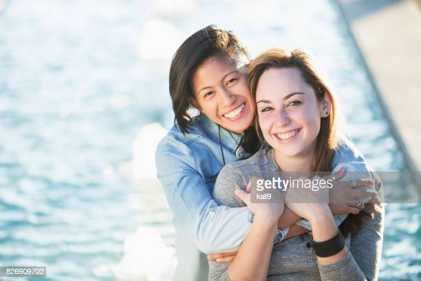 Young lesbian couple posing, in sunlight