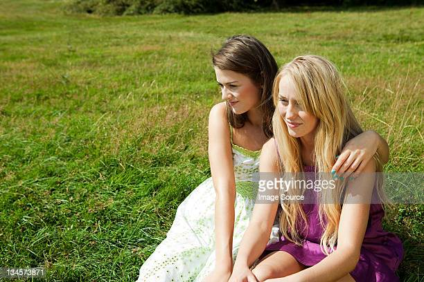 young lesbian couple sitting side by side in a field - only young women stock pictures, royalty-free photos & images