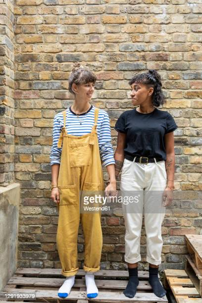 young lesbian couple smiling while standing on bench against brick wall - couple relationship stock pictures, royalty-free photos & images