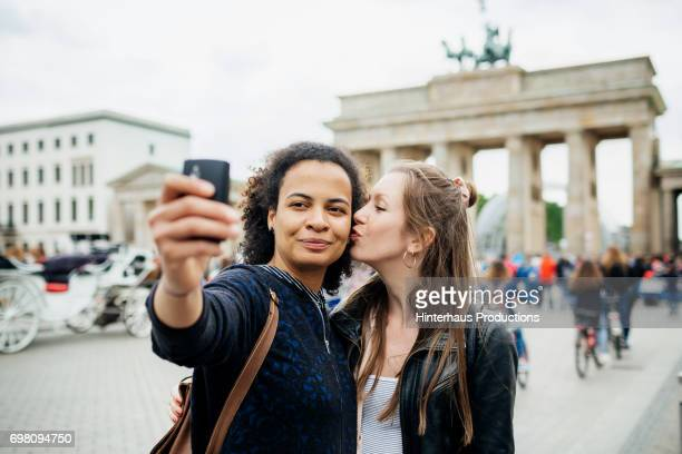 young lesbian couple stop to take a selfie at brandenburg gate in berlin - lesbica bacio foto e immagini stock