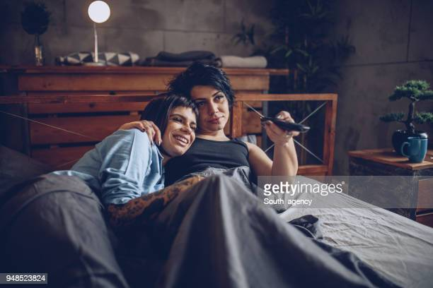 jeune couple lesbien, regarder la télévision au lit - couple au lit photos et images de collection