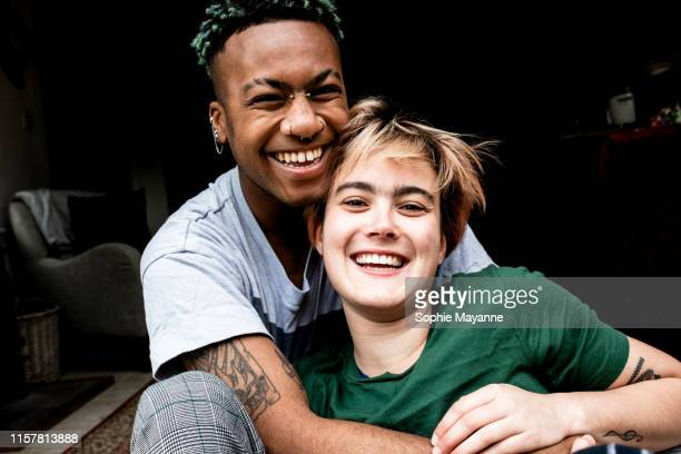 A young LGBT couple laughing and hugging