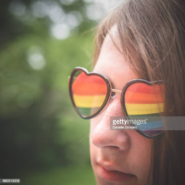 Young LGBTQ person's heart-shaped glasses reflecting pride flag colors