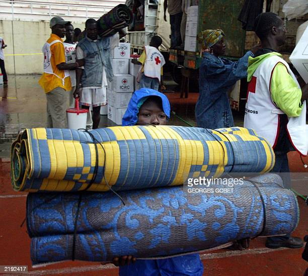 A young Liberian boy displaced by war carries goods in Samuel Kanyon Doe stadium in Monrovia 14 July 2003 distributed by the International Red Cross...