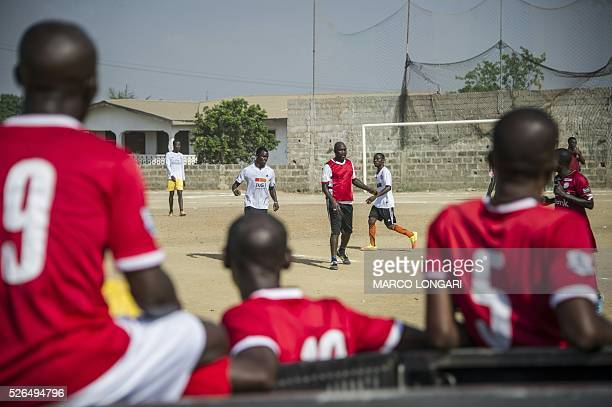 Young Liberian players look from the sideline as international Liberian football star, George Weah plays a match on a dusty pitch at the Alpha Old...