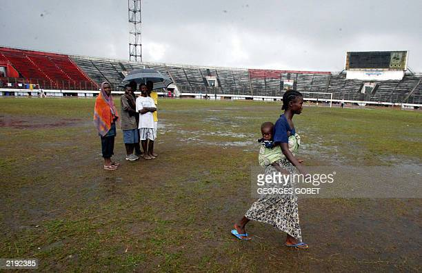 A young Liberian woman and her baby displaced by war crosses the Samuel Kanyon Doe stadium pitch in Monrovia 14 July 2003 to fetch goods and food...