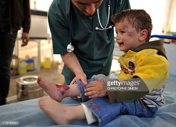 A young Libyan boy is treated at a hospital after he was lightly wounded from shelling by Moamer alKadhafi's forces overnight in the Ras Amar area of...