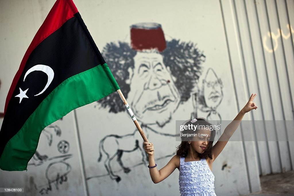 A young Libyan girl waves a flag in front of anti-Gaddafi graffiti scrawled on an underpass wall on August 29 2011 in Tripoli, Libya.
