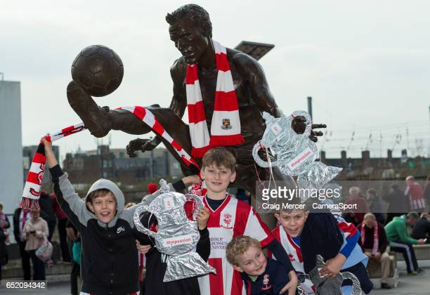 Young Lincoln City fans decorate the Dennis Bergkamp statue with their sides colours ahead of the Emirates FA Cup QuarterFinal match between Arsenal...
