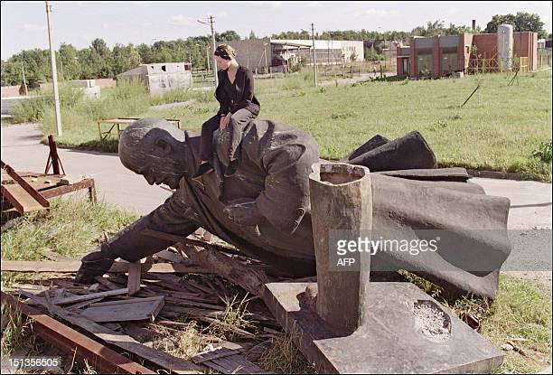 A young Lithuanian girl sits on the toppled statue of Russian Bolshevik revolutionary leader Vladimir Ilyich Lenin 01 September 1991 in Vilnius after...