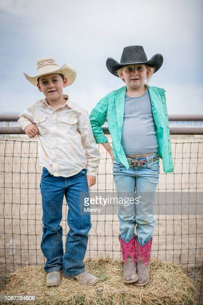 Young little cowboy and cowgirl at rodeo fence portrait