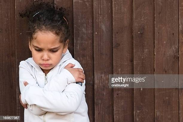 Young little girl with arms crossed and sad