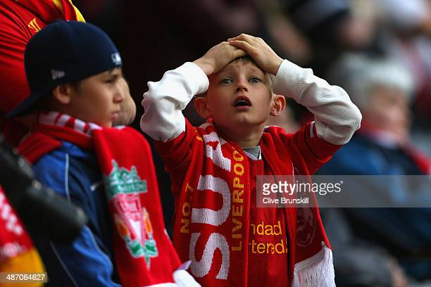 A young Liverpool fan reacts during the Barclays Premier League match between Liverpool and Chelsea at Anfield on April 27 2014 in Liverpool England