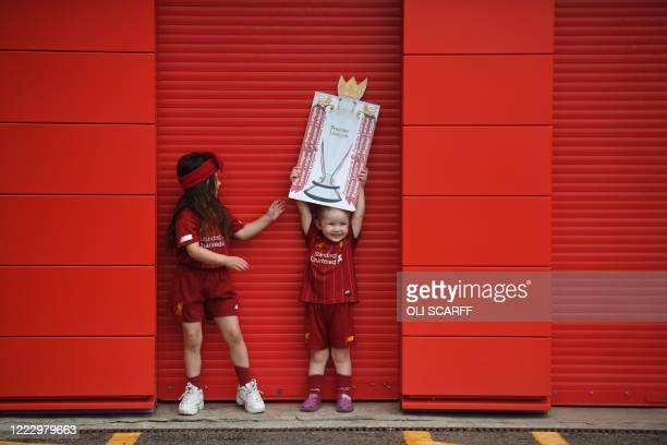 Young Liverpool fans Kendall and Sadie pose with a Premier League trophy placard outside as they celebrate Liverpool sealing the Premier League title...