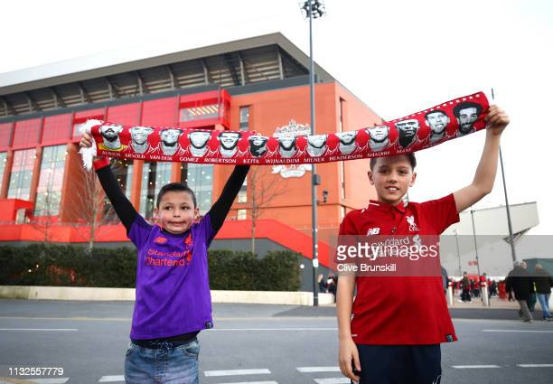 Young Liverpool fans pose for a picture outside the stadium prior to the Premier League match between Liverpool FC and Watford FC at Anfield on...