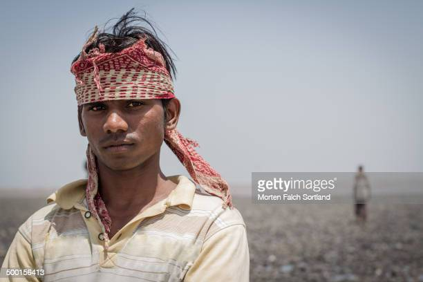Young, local Indian man posing for the camera at the beach in Daman, Gujarat, a former Portuguese colony. In the background, one can se a woman...