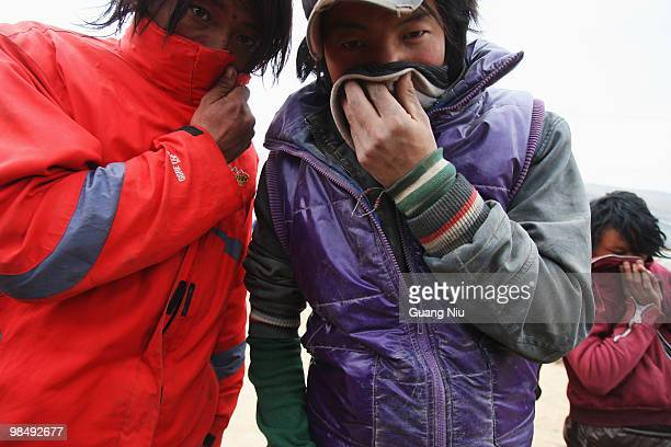 Young locals cover their faces as soldiers and rescue workers continue efforts to save people from collapsed buildings on April 16 in Golmud, China....