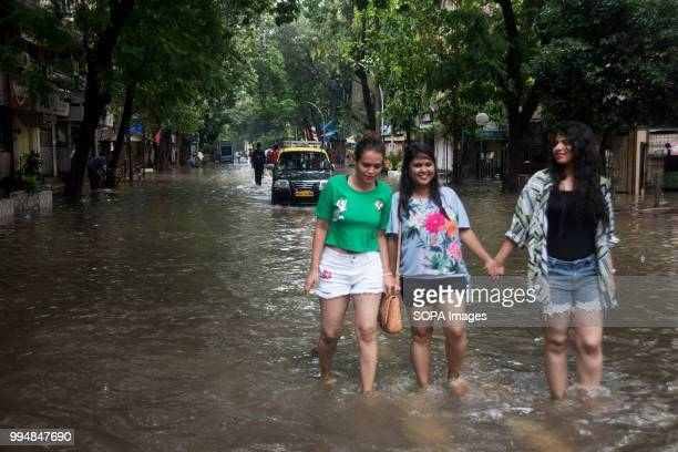 DADAR MUMBAI MAHARASTRA INDIA Young locals seen walking through a flooded street Heavy rains across Mumbai city and adjoining areas continue for 3rd...