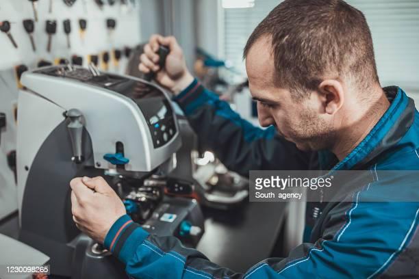 jonge slotenmaker die autosleutel met sleutelkopiemachine kopieert - locksmith stockfoto's en -beelden