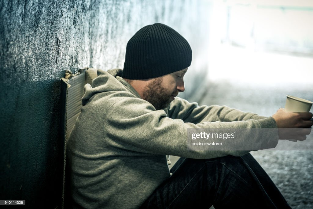 Young lonely homeless man sitting in dark subway tunnel : Stock Photo