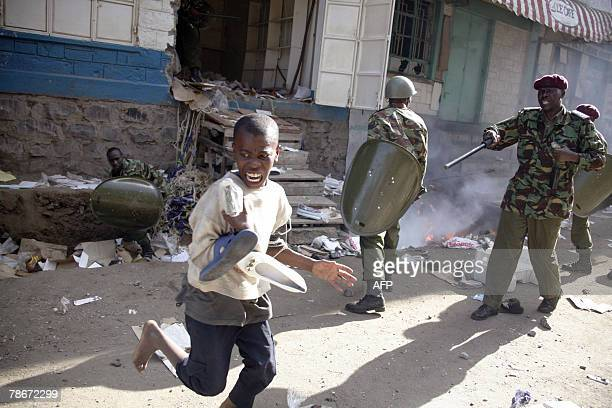 A young looter carries some stolen shoes past Kenyan riot police during disturbances in the Mathare neighborhood 29 December 2007 in Nairobi Kenya...
